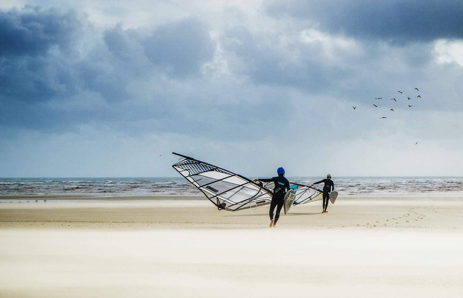 windsurfers walking towards ocean