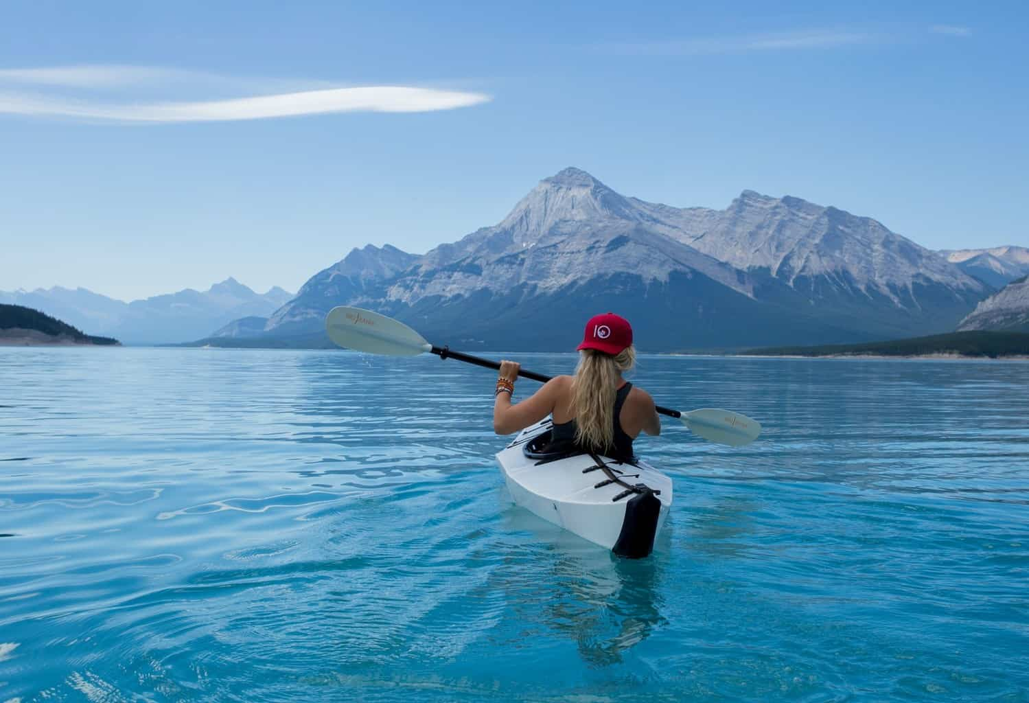 woman kayaking on blue lake